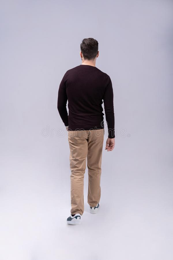 Full length portrait of a smiling young man walking isolated over gray background. royalty free stock photography