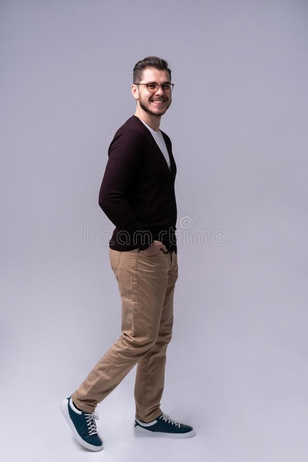 Full length portrait of a smiling young man walking isolated over gray background. stock image