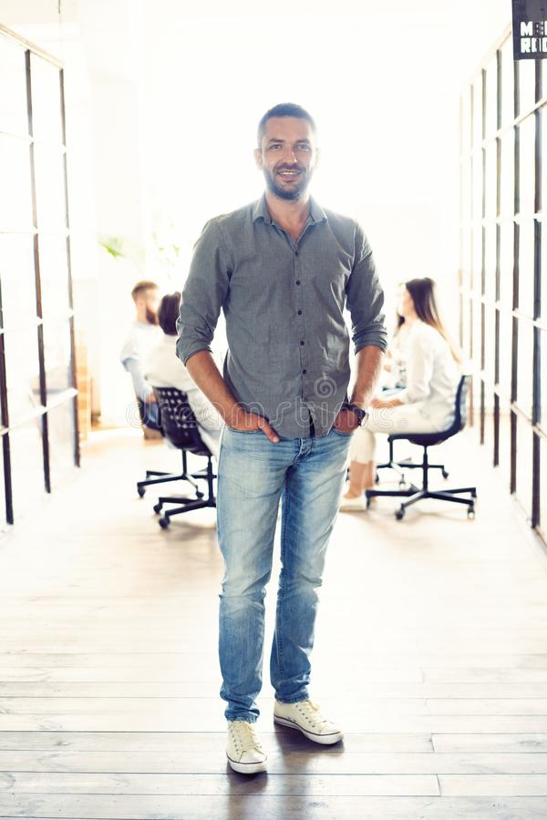 Full length portrait of smiling young man standing in doorway of office. Creative male executive at startup with people stock photo