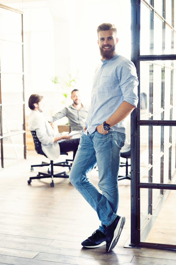 Full length portrait of smiling young man standing in doorway of office. Creative male executive at startup with people royalty free stock photo