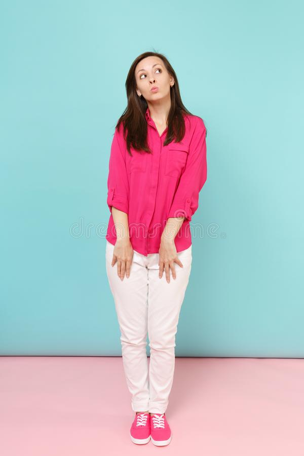 Full length portrait of smiling young pretty woman in rose shirt blouse, white pants posing isolated on bright pink blue stock photo