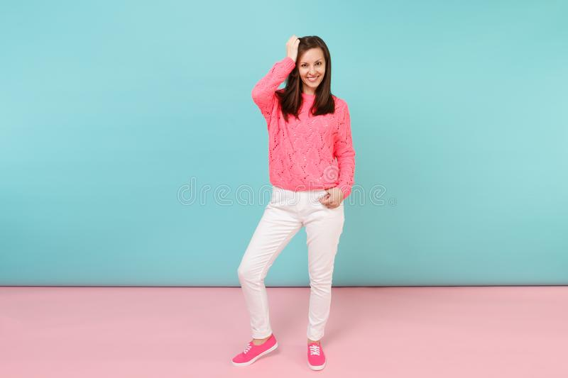Full length portrait of smiling young woman in knitted rose sweater, white pants posing isolated on bright pink blue. Pastel wall background in studio. Fashion stock photos