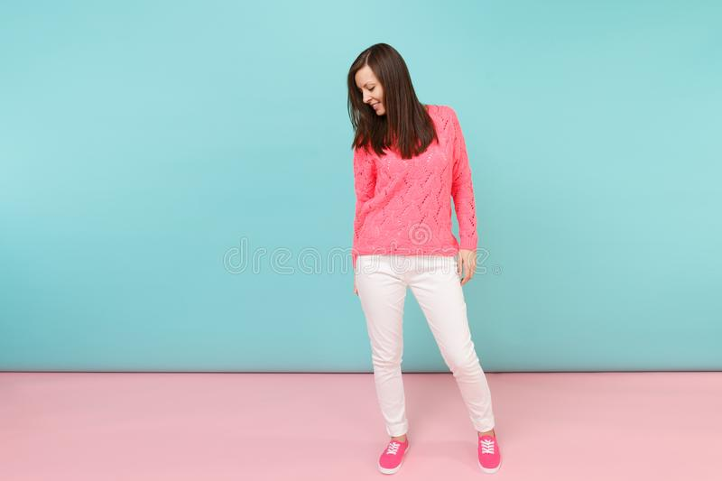 Full length portrait of smiling young woman in knitted rose sweater, white pants posing isolated on bright pink blue. Pastel wall background in studio. Fashion stock images