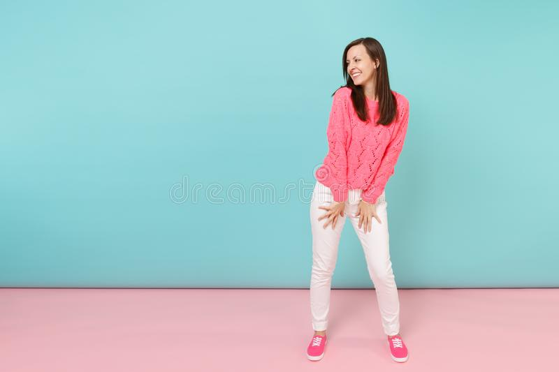 Full length portrait of smiling young woman in knitted rose sweater, white pants posing isolated on bright pink blue. Pastel wall background in studio. Fashion stock image