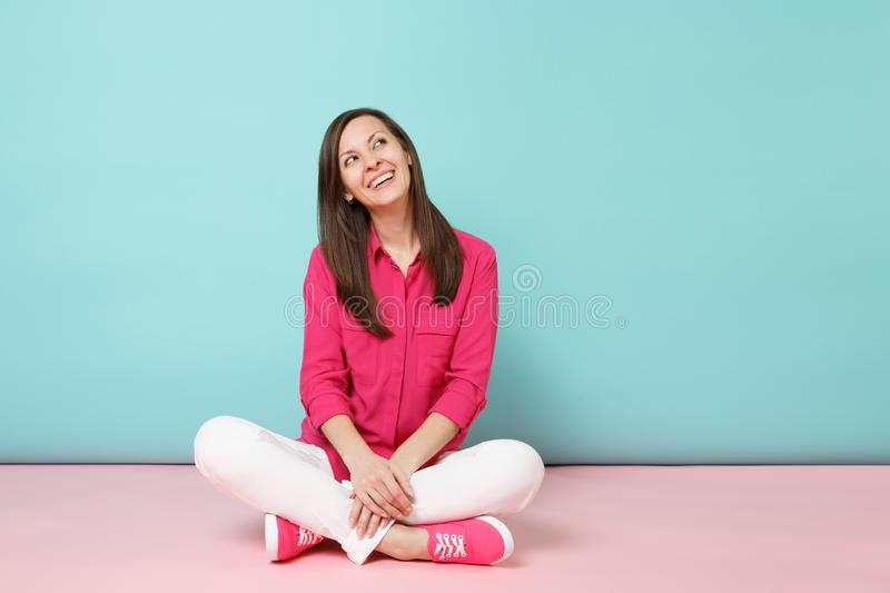 Full length portrait of smiling young woman in rose shirt blouse, white pants sitting on floor isolated on bright pink. Blue pastel wall background studio stock images