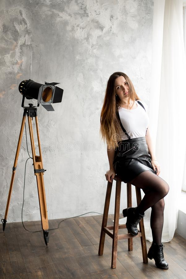 Full length portrait of a smiling young woman sitting on chair stock photography