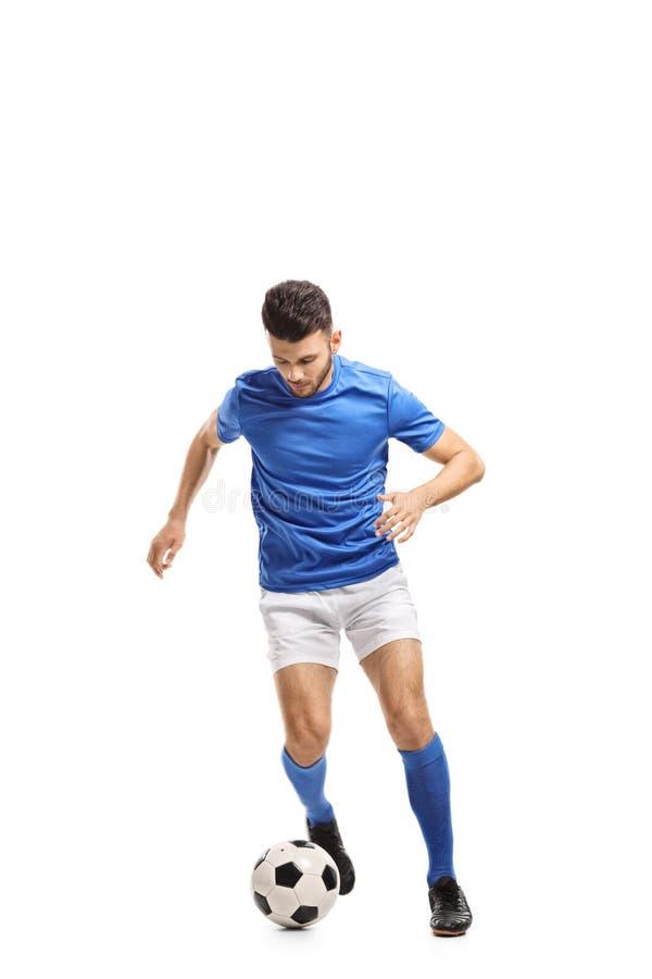 Soccer player dribbling. Full length portrait of a soccer player dribbling isolated on white background royalty free stock image