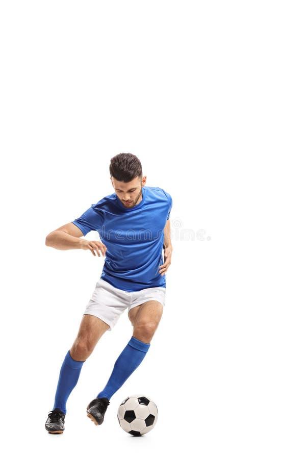 Soccer player dribbling. Full length portrait of a soccer player dribbling isolated on white background stock image