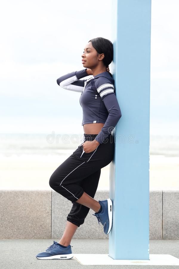 Full length sporty young black woman leaning against pole outside royalty free stock photos