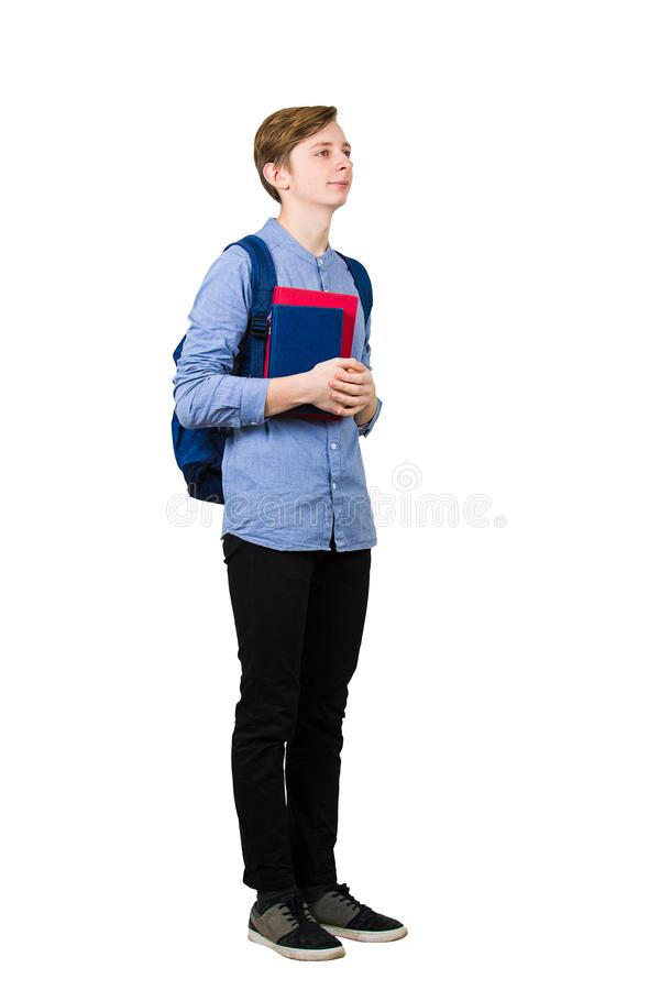 Full length portrait of student boy holding two books to chest and carrying his backpack. Teenage guy back to school isolated on royalty free stock image