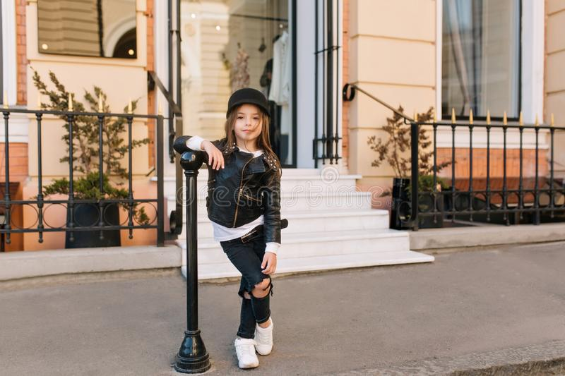 Full-length portrait of stylish kid standing with legs crossed next to iron pillar in front of shop. Charming elegant stock photos