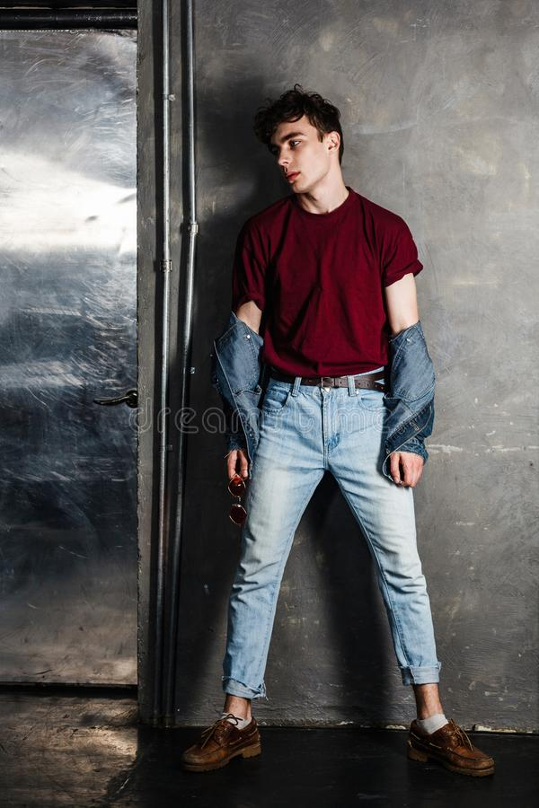 Full length portrait of stylish young fashion model man in bright red sunglasses and denim casual style posing near metallic door royalty free stock photography