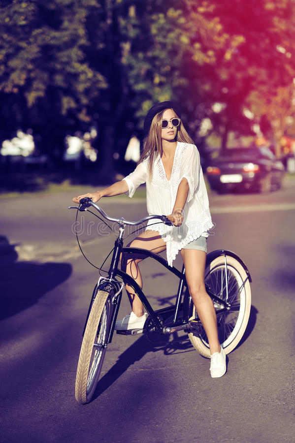Full length portrait of stylish young woman on a bike royalty free stock images