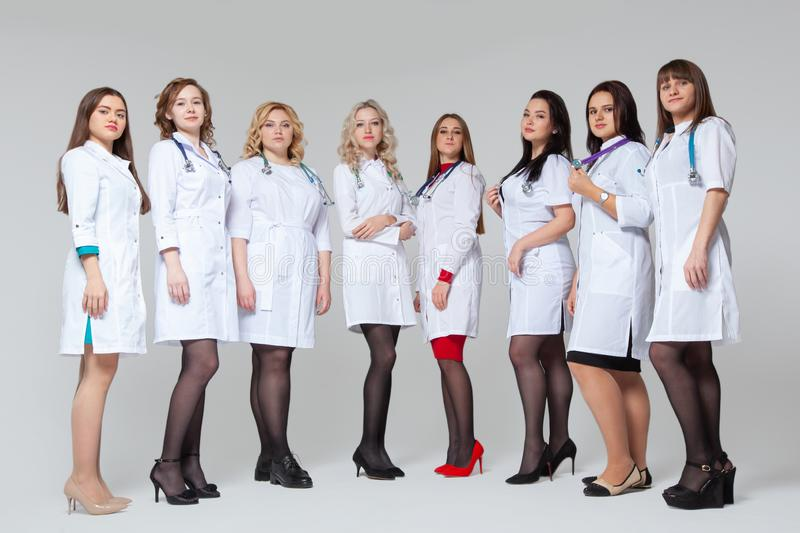 Full length portrait of a successful group of doctors staying in front of grey background stock photos