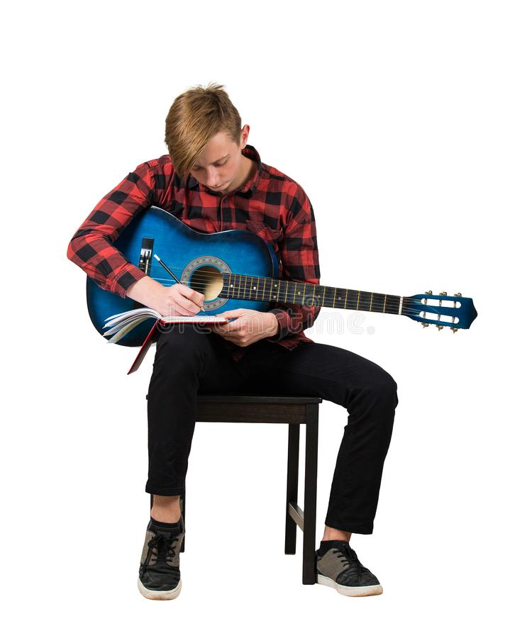 Full length portrait of talented boy music composer with his trendy acoustic guitar seated on chair thinking to write a new song royalty free stock photos