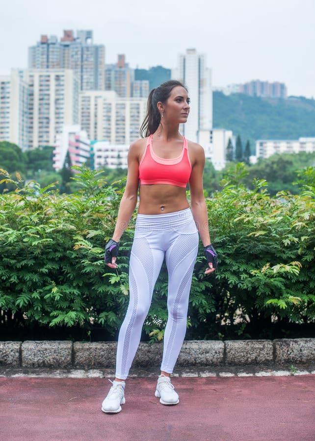 Full length portrait of tanned slim fitness brunette model wearing sports bra and leggings standing in the city park royalty free stock photos