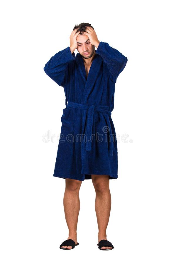 Full length portrait of tardy young man wears blue bathrobe holding hands to head, unable to wake up in time to get to work, royalty free stock photo