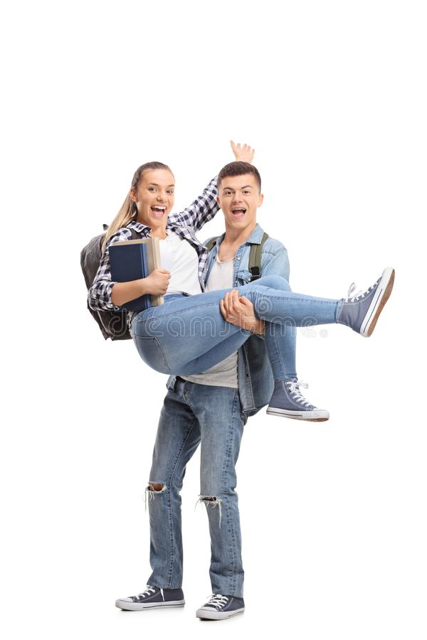 Full length portrait of a teenage boy carrying a girl in his han royalty free stock images