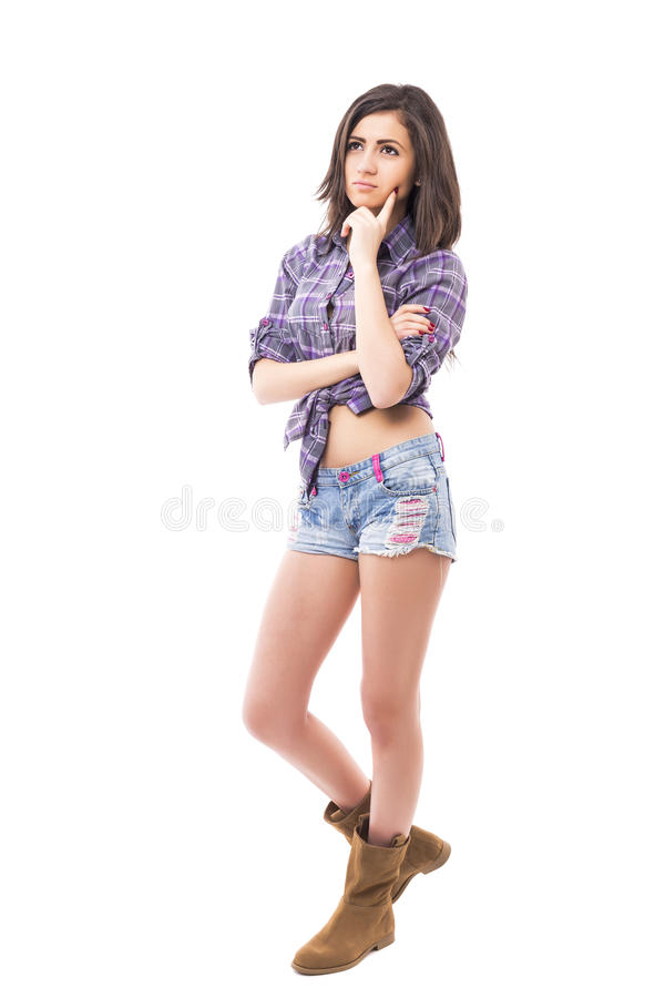 Full length portrait of thoughtful beautiful teenage girl thinking hard royalty free stock photography