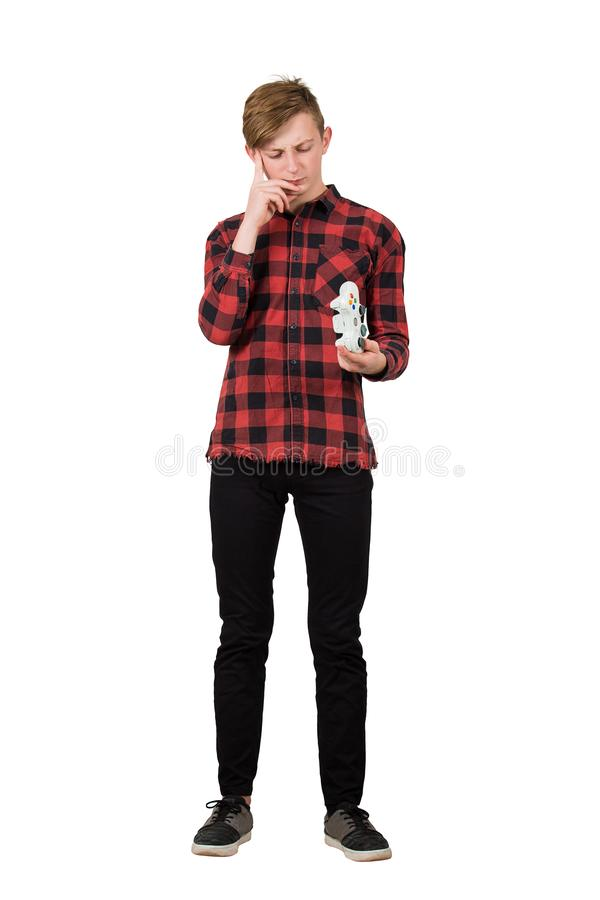 Full length portrait thoughtful and upset teenager has problems playing video games, looking perplexed at the broken joystick royalty free stock images