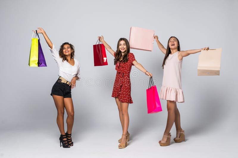 Full length portrait of three excited young multiethnic women with shopping bags isolated on white royalty free stock photography