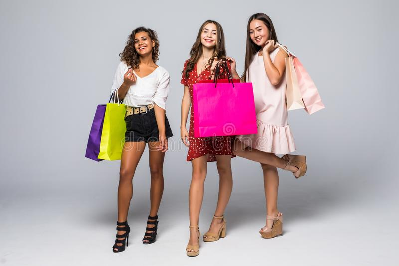 Full length portrait of three excited young multiethnic women with shopping bags isolated on white royalty free stock images