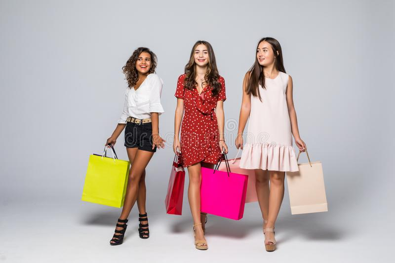 Full length portrait of three excited young multiethnic women with shopping bags isolated on white stock photography