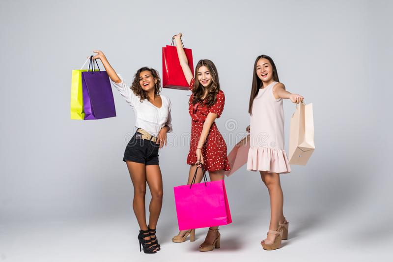 Full length portrait of three excited young multiethnic women with shopping bags isolated on white stock image