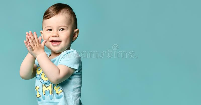 Full length portrait of a toddler boy in a blue summer cotton suit isolated in a turquoise background. royalty free stock images