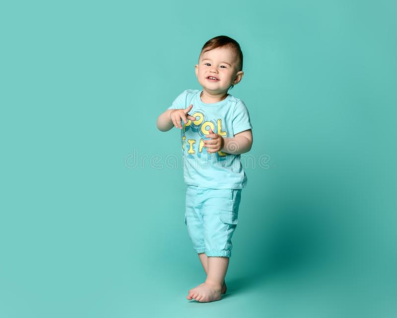 Full length portrait of a toddler boy in a blue summer cotton suit isolated in a turquoise background. royalty free stock image