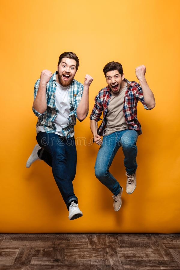 Full length portrait of a two excited young men celebrating. While jumping together isolated over yellow background royalty free stock photography