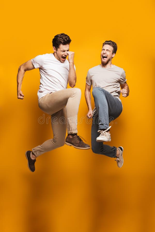 Full length portrait of a two excited young men. Best friends jumping and celebrating isolated over yellow background royalty free stock images