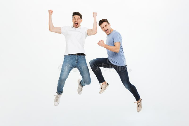 Full length portrait of two excited young men jumping. And celebrating success isolated over white background royalty free stock image