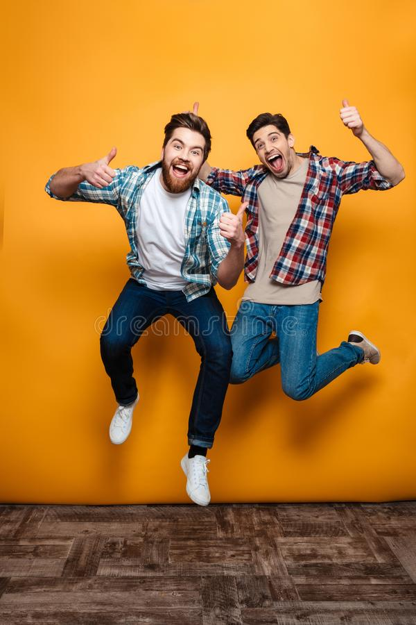 Full length portrait of a two happy young men celebrating stock photography
