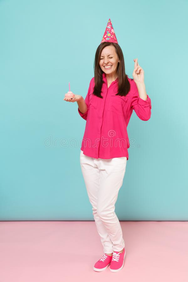 Full length portrait woman in rose shirt blouse, white pants, birthday hat with cupcake posing isolated on bright pink. Full length portrait woman in rose shirt stock photos