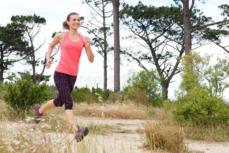 Full length portrait of woman smiling while running trail outside stock photography