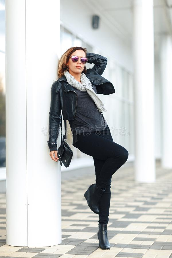 Full-length portrait woman in sun glasses a black leather jacket, black jeans leans on a pillar holding up one leg in front of mir stock photography