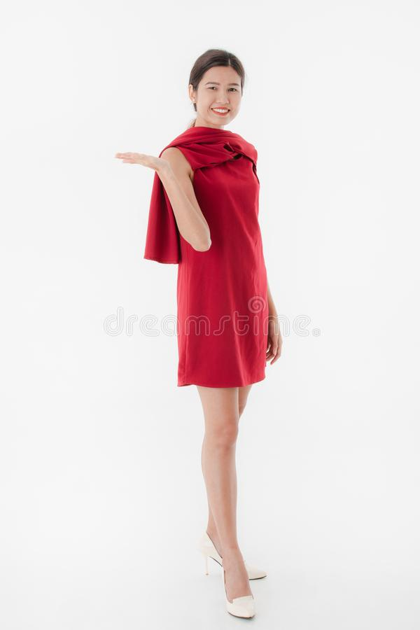 Young lady in red dress. Full length, portrait of young beautiful, attractive Asian woman in stylish red short dress, high heel, smiling, playfully posing stock photography