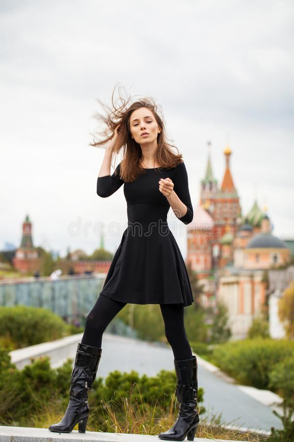 Portrait of young beautiful woman in black dress posing in autumn park on a background of Red Square in Moscow royalty free stock image