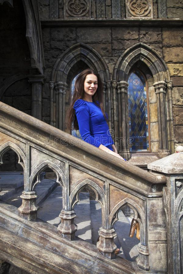Portrait young beautiful brunette woman in blue dress posing against the backdrop of an old castle in the Gothic style. Full-length portrait young beautiful stock image
