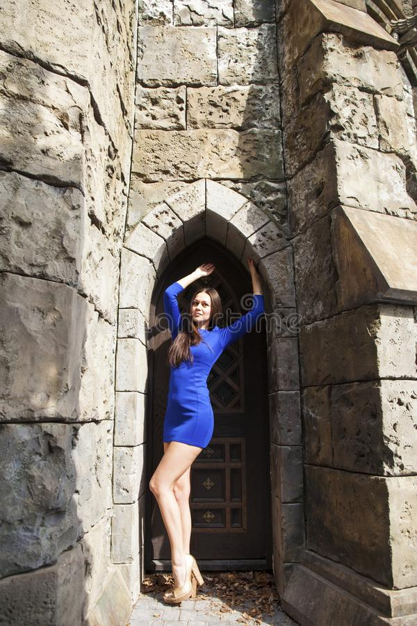 Portrait young beautiful brunette woman in blue dress posing against the backdrop of an old castle in the Gothic style. Full-length portrait young beautiful royalty free stock image
