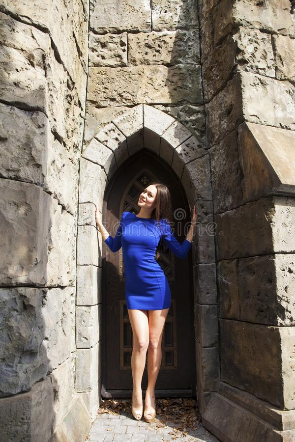 Portrait young beautiful brunette woman in blue dress posing against the backdrop of an old castle in the Gothic style. Full-length portrait young beautiful royalty free stock photography
