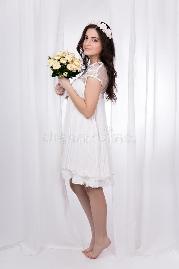 full length portrait of young beautiful happy woman in white bridal dress with flowers stock photography