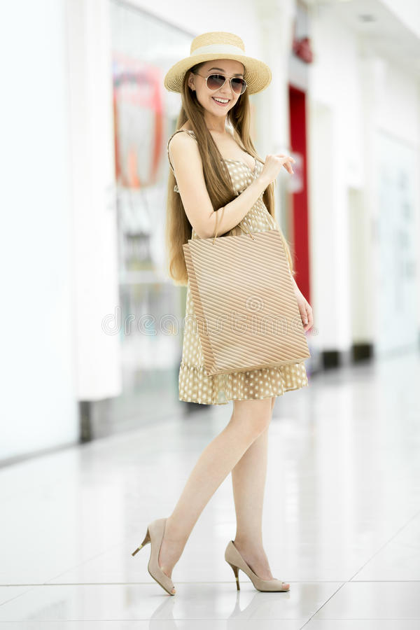 Full length portrait of young beautiful shopper woman. Full length portrait of young pretty long-haired woman standing in shopping centre wearing hat, cute royalty free stock photos