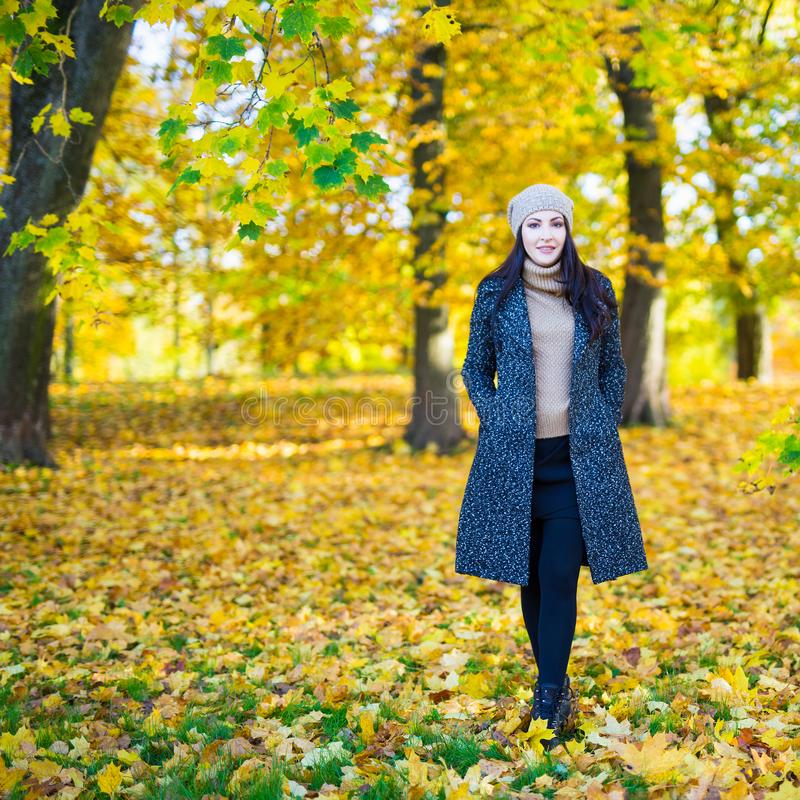 Full length portrait of young woman in autumn park royalty free stock images