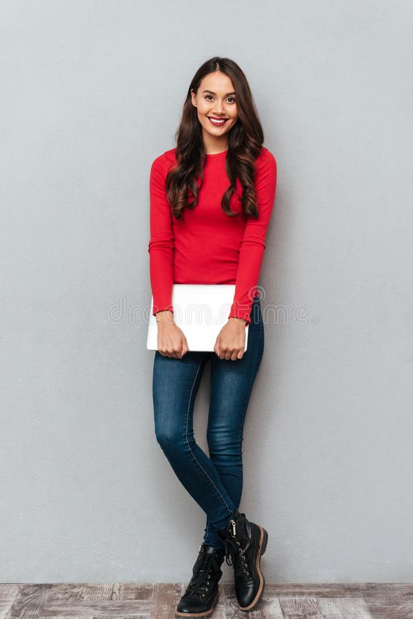 Full length portrait of young beautiful woman in casual wear holding laptop, looking at camera royalty free stock photography