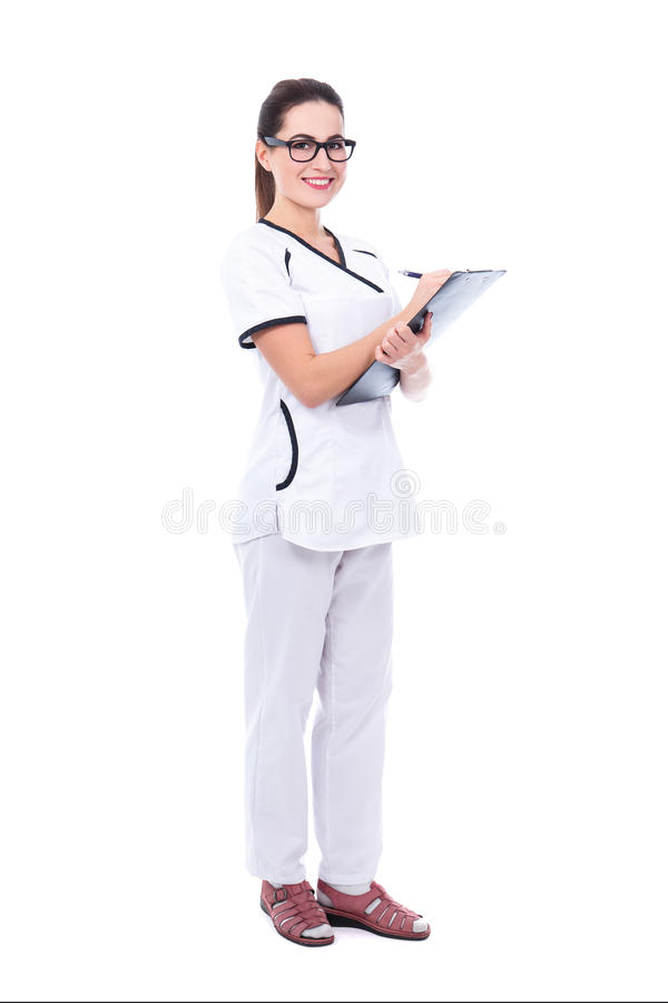 full length portrait of young beautiful woman doctor writing something on clipboard isolated on white royalty free stock photography