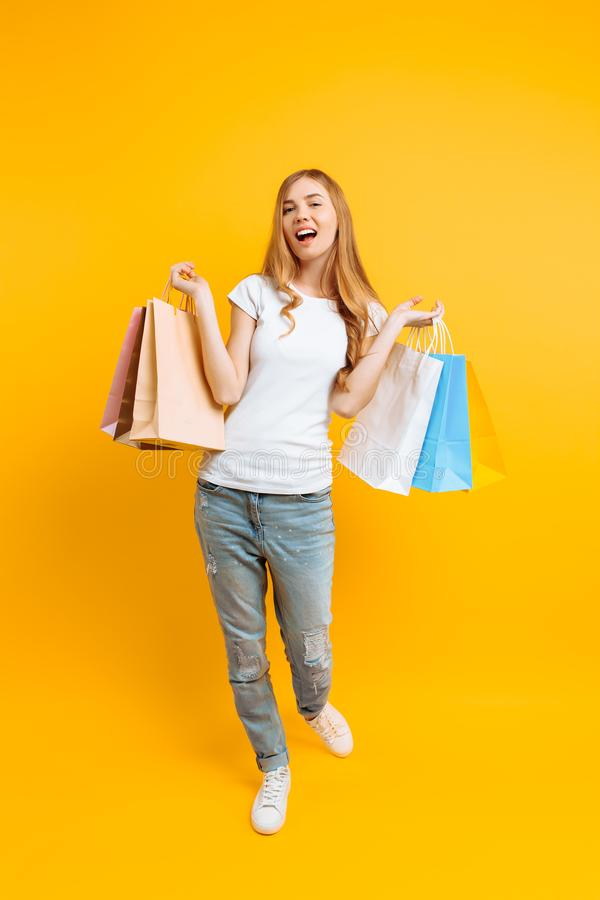 Full-length portrait of a young beautiful woman , with multi-colored bags, on a yellow background royalty free stock photography