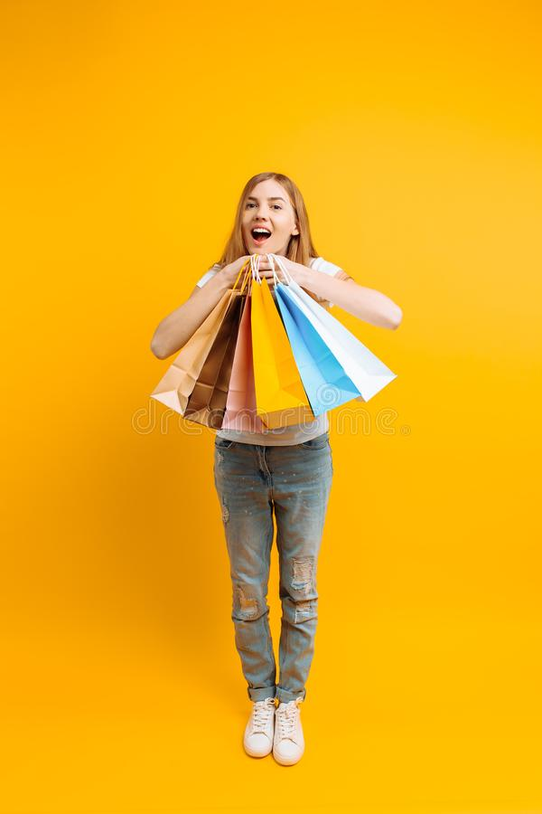 Full-length portrait of a young beautiful woman , with multi-colored bags, on a yellow background stock images
