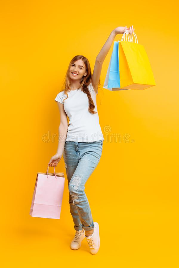 Full-length portrait of a young beautiful woman , with multi-colored bags, on a yellow background royalty free stock photo
